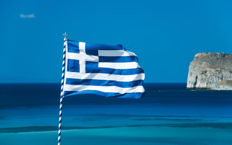 Bandiera greca che sventola con sfondo il mare